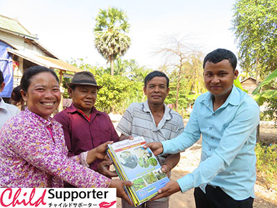 FH staff providing the agriculture books to village chief and HGV-A in Boeung Mealea village.1.jpg