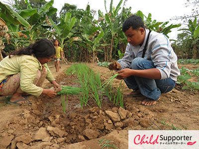 WEB_A villager planting vegetables and FH staff coaching and helping her.jpg